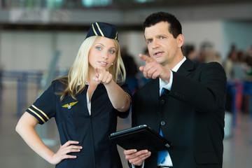 Business-Mann zeigt Stewardess etwas in der Luft