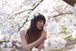 junge frau steht unter kirschblütenzweige