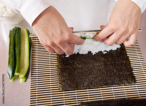cook making   sushi rolls  with cucumber