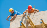 Construction workers nailing cement formwork in place poster