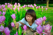 Cute Thai girl hiding among pink Siam Tulip