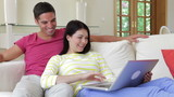 Couple Sitting On Sofa Using Laptop Computer
