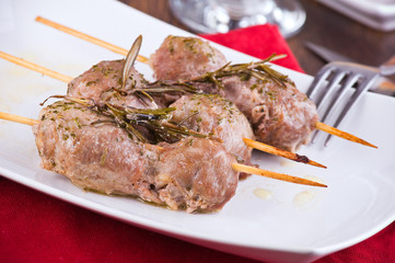 Meat skewers on white dish.