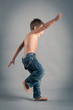 Young boy jumping. Studio portrait with grey background.