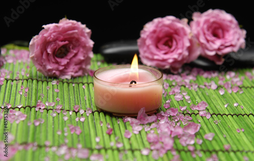 Beautiful pink rose and zen stones with candle in green mat