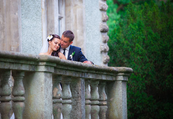 Newlywed couple kissing on building balcony