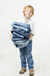 Child holding jeans stack. Kids clothing fashion. White backgrou