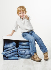 Child on cardboard box packed with jeans. Showing thumbs up