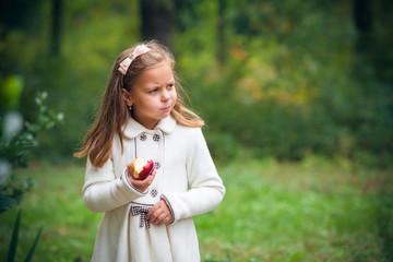 little girl is eating apple outdoor
