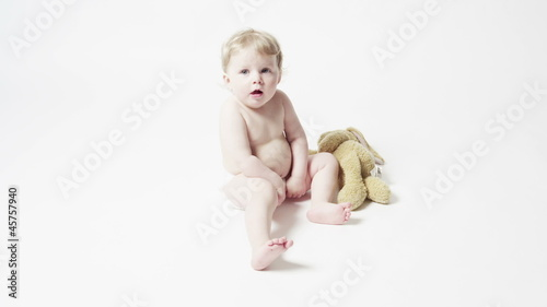 Baby Girl Sitting on a White Rug with her Toy