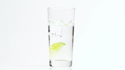 Dropping a Lime in a Glass of Water in Slow Motion
