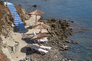 blue stairs to tranquil beach with umbrellas and chairs