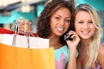 two young women after shopping, one is calling someone