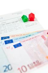 Sparbuch mit Banknoten und Modelhäusern