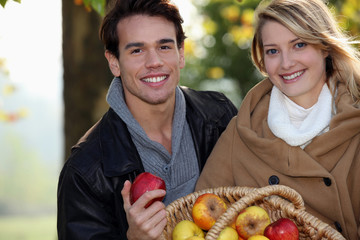 couple gathering apples in the garden