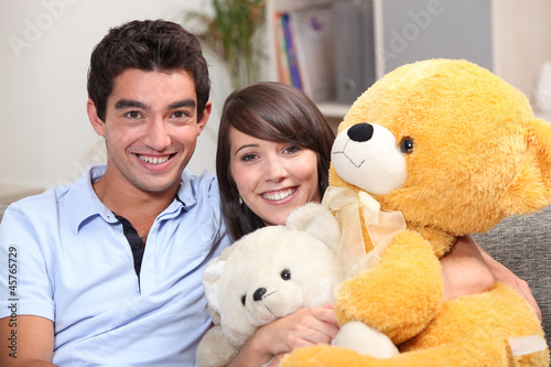 Young couple sat with giant teddy bear