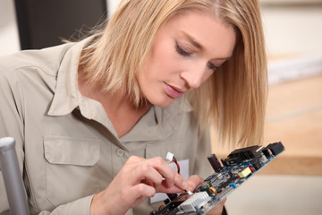 woman repairing electronic piece