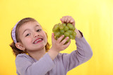 Little girl holding bunch of green grapes
