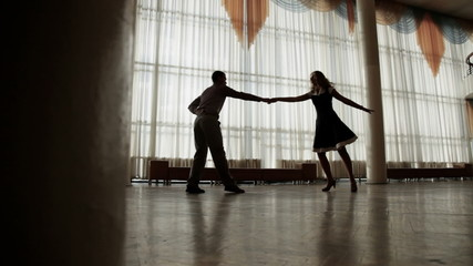 Attractive couple training to dance together