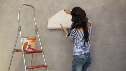 Beautiful woman gluing wallpaper on wall