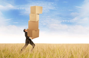 Businessman carrying heavy boxes outdoor