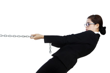 Businesswoman pulling metal chain isolated in white