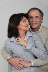 A middle age couple hugging.