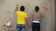 Lovely couple holding by hands and painting wall