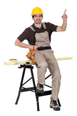 a carpenter pointing up and showing something