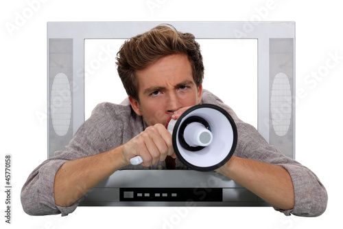 Man with megaphone coming through television