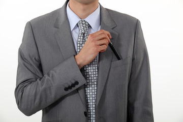 Businessman putting a pen in his pocket