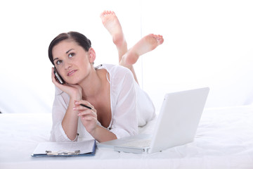young pretty girl phoning and using her laptop