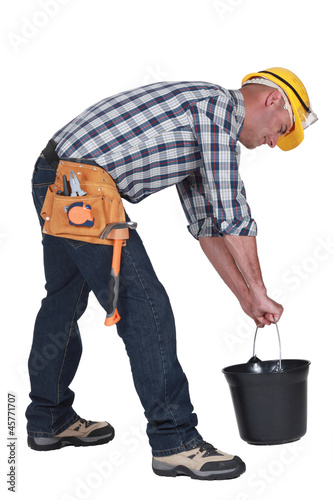 Worker lifting plastic bucket