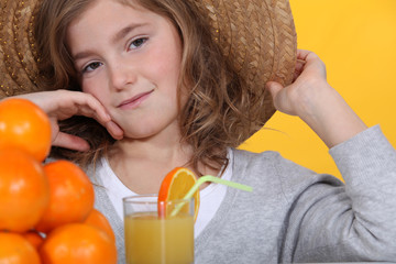 Little girl wearing hat drinking glass of orange juice