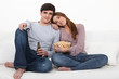 Couple relaxing on sofa with beer and popcorn