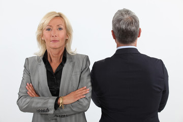 Smart mature businesswoman next to businessman