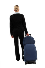 studio shot of businesswoman pulling luggage