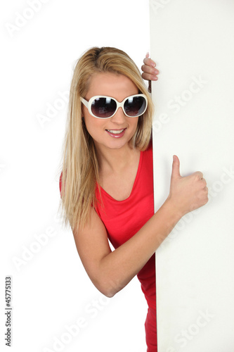 Woman with sunglasses hiding behind white panel