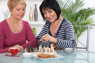 Female friends playing chess over coffee