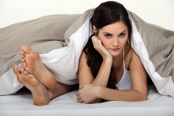Annoyed woman in bed next to her partner's feet