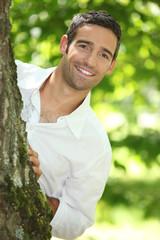 Peekaboo. Man in a white shirt peering round a tree.