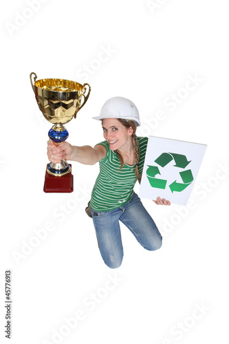 Woman jumping and holding a trophy and a recycle symbol