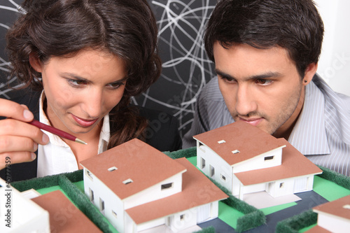 Two architect looking a miniature housing model