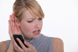 woman trying to hear a person on her cell phone
