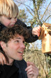 Father and son stood by bird-house