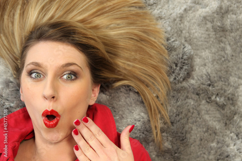 Shocked woman laying on carpet