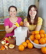 women  making fresh orange juice