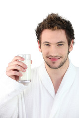 Man in dressing gown drinking glass of milk