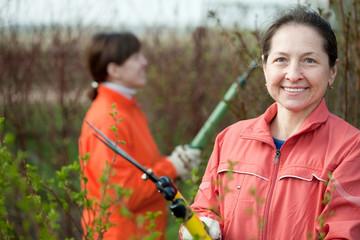 women pruned branches in the garden