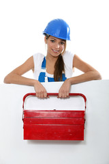 Female labourer with tool box stood behind message board